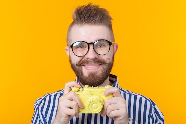 口ひげとあごひげを持つかわいい若い男性写真家が黄色のビンテージカメラを撮影しています