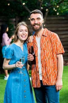 Симпатичный молодой мужчина и женщина с напитками смеется