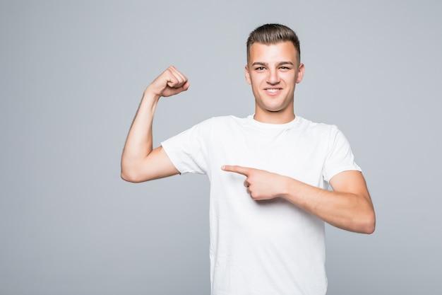 かわいい若い男の男の子は白い壁に隔離された彼の筋肉の体を示しています