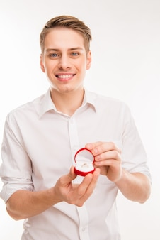 Cute young man holding red box with wedding ring and making proposition