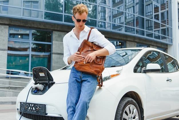 Милый молодой человек возле современного электромобиля. концепция экологического транспорта.