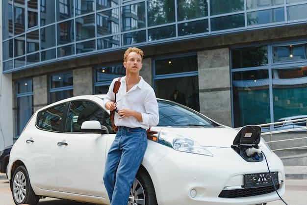 현대 전기 자동차 근처에 귀여운 젊은 남자. 생태 교통의 개념입니다.