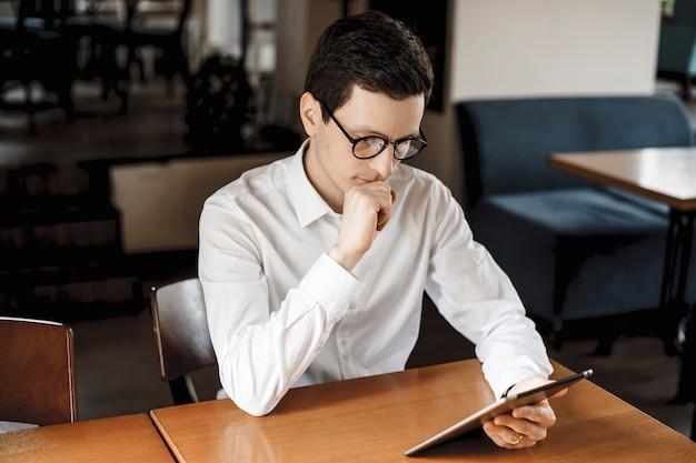机に座って、白いシャツと眼鏡をかけてタブレットを見ているかわいい若い男。