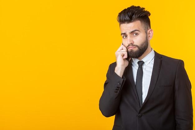 Симпатичный молодой человек с бородой в строгой одежде разговаривает по телефону, позирует на желтой стене