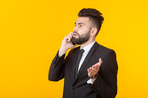 Cute young man with a beard in formal clothes talking on the phone posing on a yellow wall