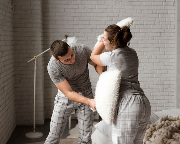 Cute young man and woman pillow fighting indoors