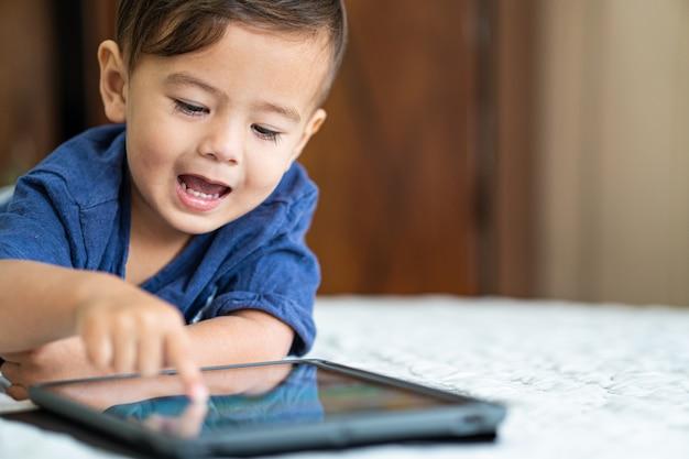 Милый молодой мальчик смешанной расы, играя с электронным устройством