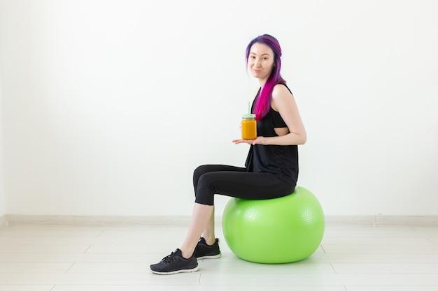 녹색 fitball에 앉아서 흰색 바탕에 그녀의 손에 바나나 단백질 스무디를 들고 색된 머리를 가진 귀여운 젊은 혼혈 hipster 소녀. 건강한 식습관과 운동 개념. copyspace