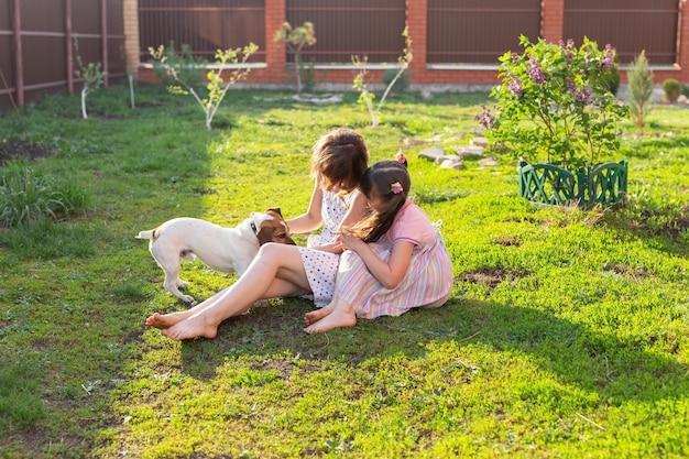 Симпатичная молодая мать и дочь сидят босиком на траве своего загородного дома рядом со своими