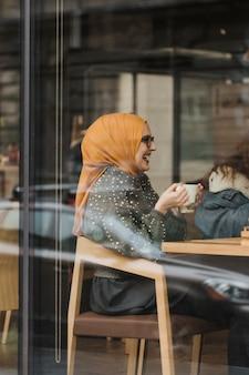コーヒーを飲んでいるかわいい若いイスラム教徒の女の子
