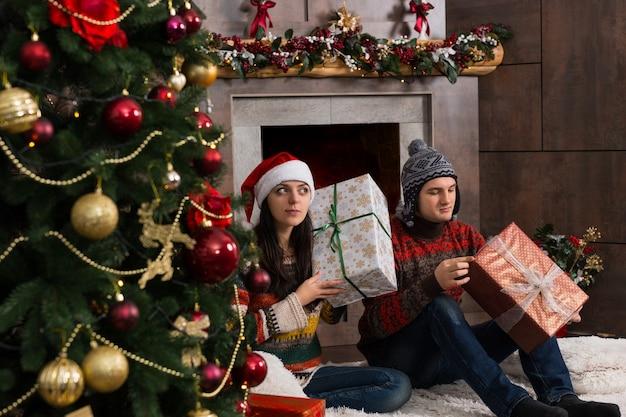 크리스마스 트리 앞 깔개에 앉아 흔들면서 상자를 귀에 대고 크리스마스 선물을 추측하는 귀여운 젊은 쌍