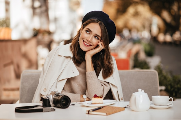 Cute young photographer, having dark wavy hairstyle, vintage beret and beige trench coat, resting at city cafe terrace with tea, cheesecake, camera and notebook on table