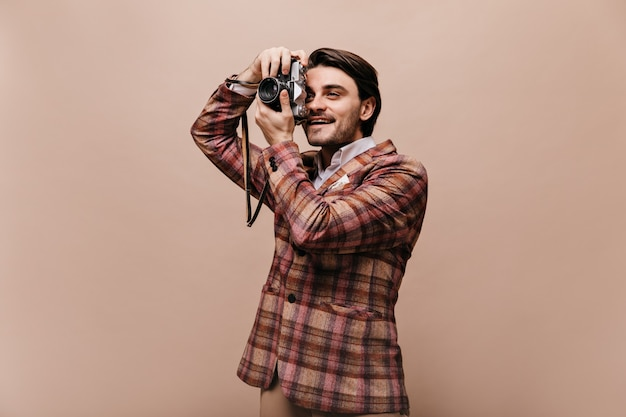 Cute young photographer with brunette hair, in trendy plaid jacket making photo and smiling