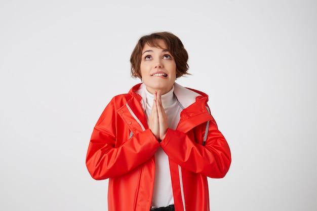 흰색 골프와 빨간 비옷에 귀여운 젊은 긍정적 인 짧은 머리 여자는 입술을 물고 복사 공간을 바라보고 행운을 바라며기도 제스처를합니다. 서 있는.