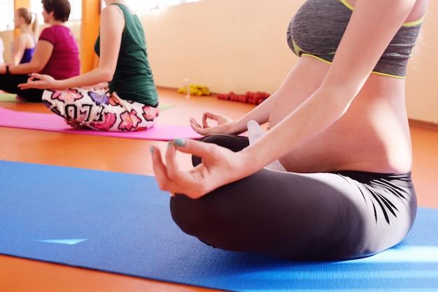 Симпатичная молодая беременная девушка занимается фитнесом вместе с группой йоги в спортивном клубе