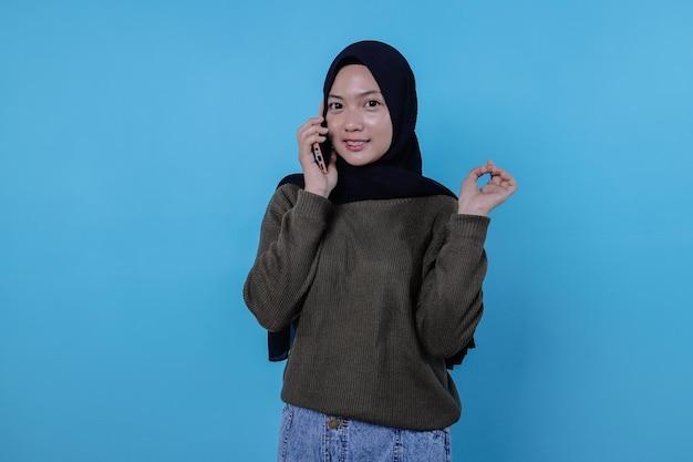 히잡을 쓰고 휴대 전화로 전화하는 귀여운 젊은 예쁜 여자