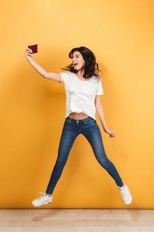 ジャンプかわいい若いきれいな女性は、電話でselfieを作る。