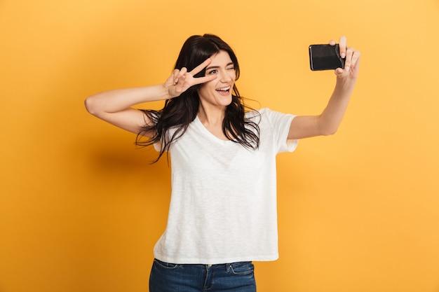 Милая молодая красивая женщина делает селфи с жестом мира по мобильному телефону.