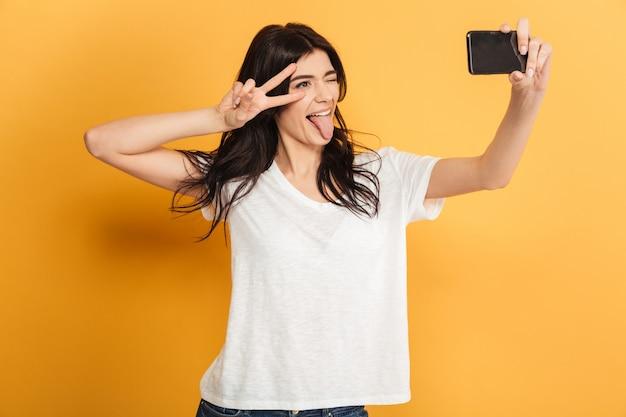 かわいい若いきれいな女性は、携帯電話で平和のジェスチャーでselfieを作る。