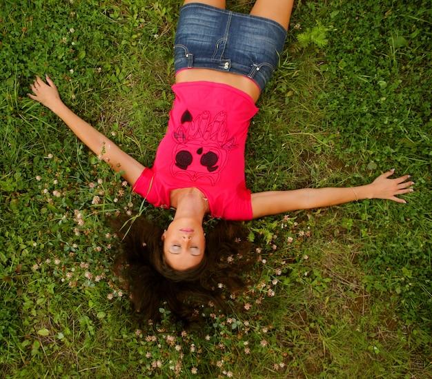 公園の芝生のフィールドに横たわっているかわいい若い赤毛の女性