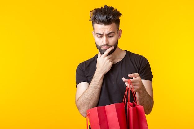 かわいい若い悲しいひげを生やした男は黄色の壁に買い物袋で購入を見て