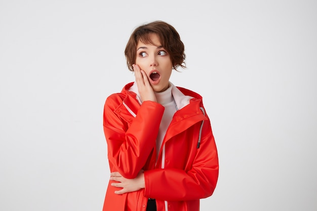 Cute young shocked short haired girl in white golf and red rain coat, looking to the left with wide open mouth, touches the cheek, hears unbelievable gossip. standing.