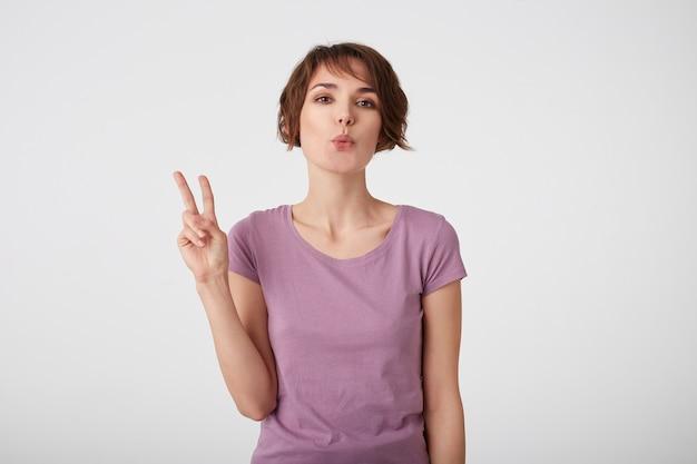かわいい若い短い髪の女性の砂のキス、手でピースサインを作り、幸せを表現し、屋内でカジュアルなシャツのポーズを着て、白い壁の上に立っています。