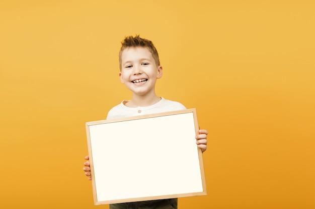 귀여운 젊은 미소 미 취학 소년 빈 흰색 빈 기호 복사 공간 격리를 들고.