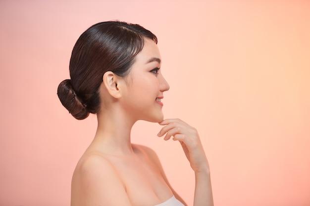 Симпатичная молодая улыбающаяся женщина трогает ее чистую кожу на фоне biege