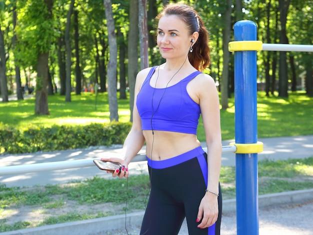Милая молодая спортивная женщина слушает музыку на прогулке