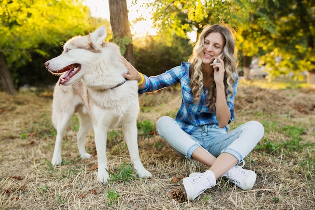 Cute young stylish pretty smiling happy blond woman playing with dog husky breed in park on sunny summer day