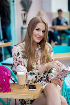 Симпатичная молодая стильная женщина, сидящая в кафе