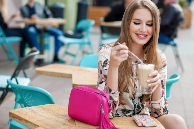 Cute young stylish woman sitting at table in cafe