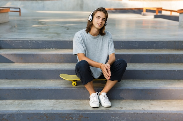 Cute young teenage boy spending time at the skate park, listening to music with headphones, sitting on skateboard