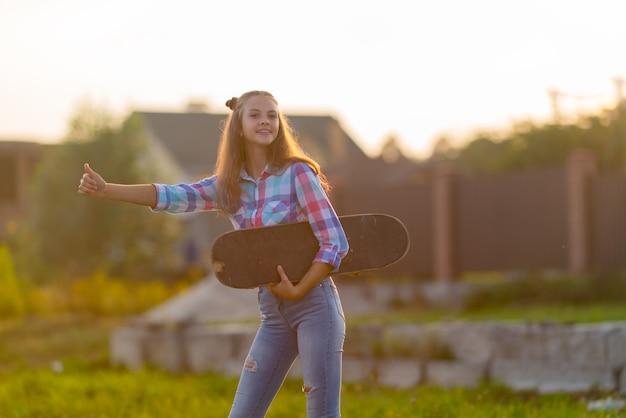 그녀의 팔 아래 스케이트 보드와 함께 타고 푼다 일몰의 따뜻한 빛에 도로의 가장자리에 서있는 리프트를 환영하는 귀여운 어린 십 대 소녀