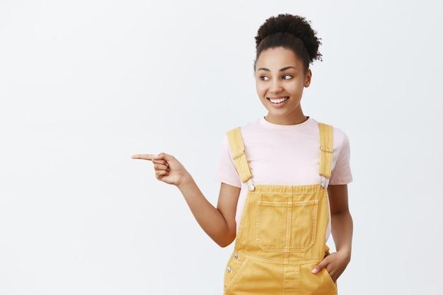 Sorella femmina giovane e tenera carina con la pelle scura in tuta gialla alla moda, tenendo la mano in tasca, indicando e guardando a sinistra