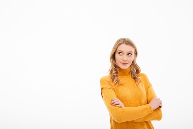 Cute young thoughtful lady standing isolated