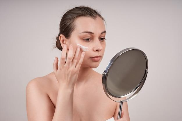 거울을 보면서 그녀의 얼굴에 영양 크림을 적용하는 귀여운 젊은 토플리스 여자는 회색 벽에 격리합니다.