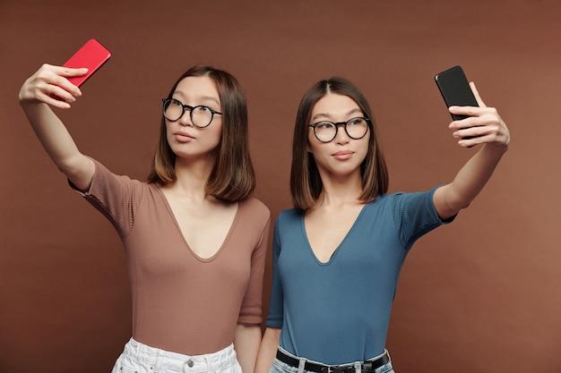 カジュアルウェアを着たかわいい若い双子の姉妹が近くに立って、自分撮りをしながら自分の前にスマートフォンを持っています