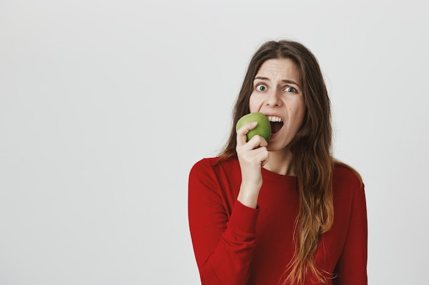 Cute young woman biting green apple and grimacing, feel toothache