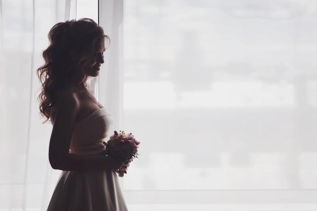 ホテルの部屋の窓に花束の花とドレスを着たかわいい若い女性の花嫁。結婚式の日の花嫁の朝。幸せな女性が新郎に会うのを待っています。幸せで贅沢な結婚の概念。コピースペース