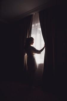 ホテルの部屋の窓に家のバスローブでかわいい若い女性の花嫁。結婚式の日の花嫁の朝。幸せな女性は彼女の新郎に会うのを待っています。幸せで贅沢な結婚の概念。コピースペース