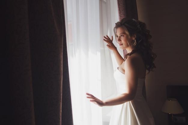ホテルの部屋の窓に白いドレスを着たかわいい若い女性の花嫁。結婚式の日の花嫁の朝。幸せな女性は彼女の新郎に会うのを待っています。幸せで贅沢な結婚の概念。コピースペース