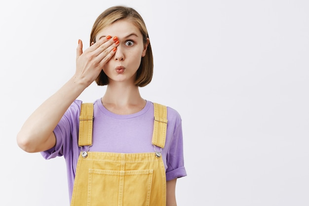 Cute young woman cover one eye and looking amazed