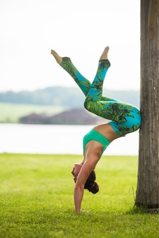 Cute young woman doing handstand exercises in the green park