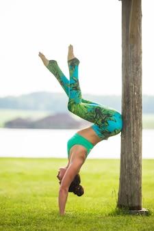 緑豊かな公園で逆立ち運動をしているかわいい若い女性