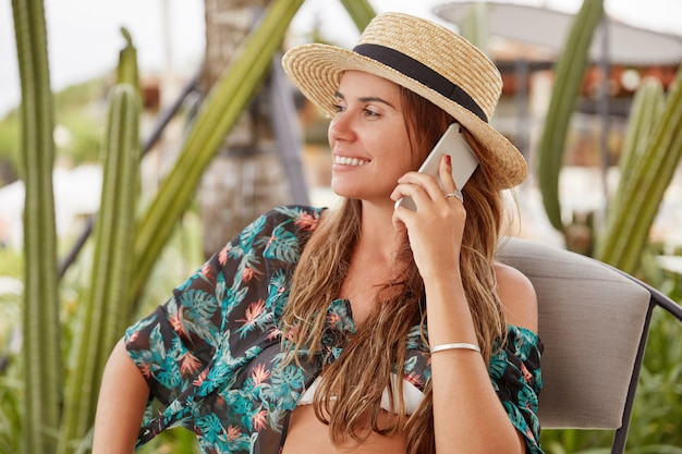 Cute young woman dressed in summer blouse and straw hat, has telephone conversation with friend, enjoys fresh air at summer resort town, looks happily aside, share positive impressions after travel