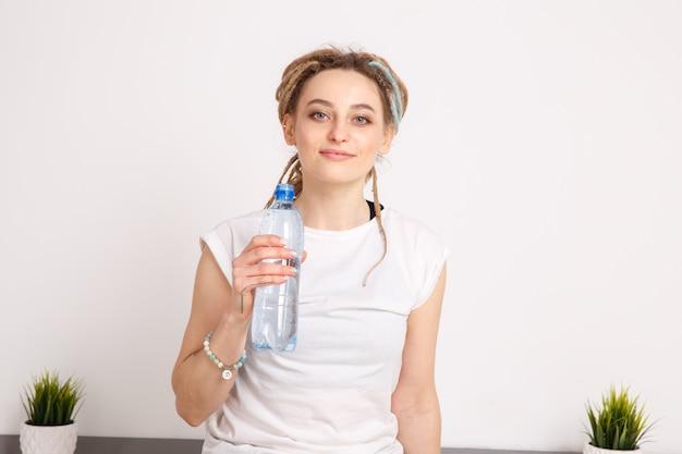 ヨガの練習中に水を飲むかわいい若い女性。