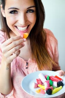 かわいい若い女性は、新鮮な笑顔でゼリーのキャンディーを食べる