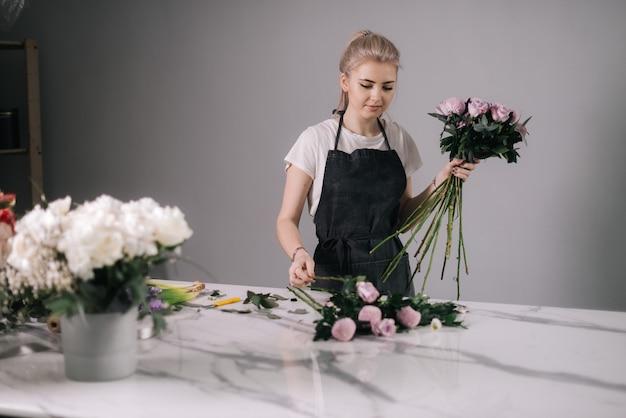 꽃꽂이를 만드는 앞치마를 입은 귀여운 젊은 여성 꽃집